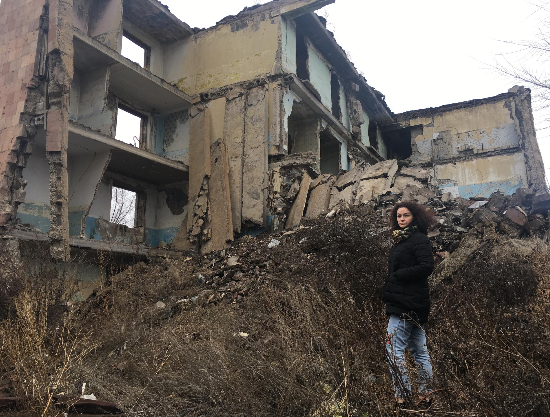 На фоне разрушенного дома в Гюмри